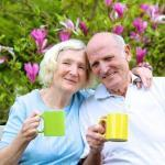 Happy mature family, loving senior couple drinking tea from big colorful mugs sitting on a wooden bench in the garden