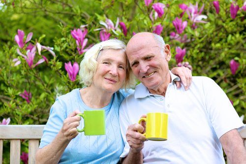 happy senior couple smiling and drinking coffee in a park or garden