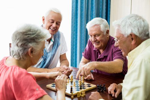 Four seniors playing chess and smiling.