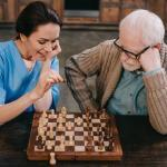 A nurse and a senior man playing chess together