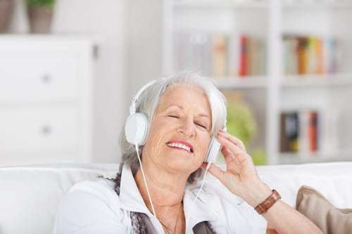 Modern senior woman listening to music on a set of headphones with her eyes closed