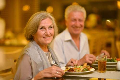 senior man and woman smiling while dining at a restaurant