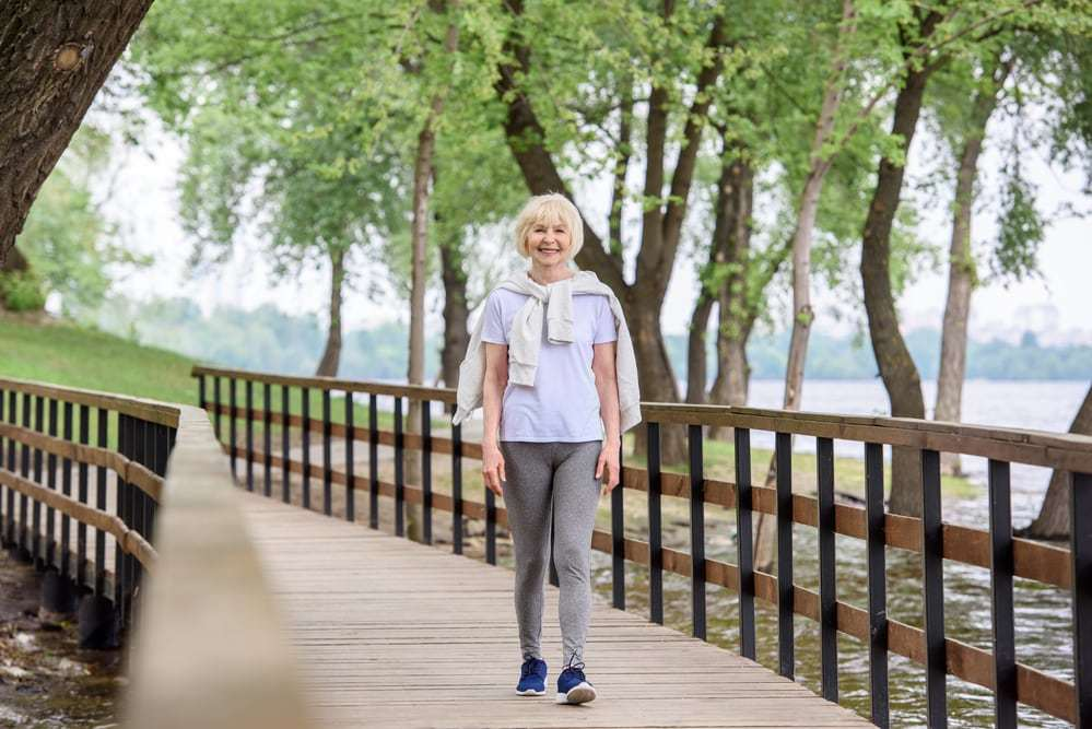 senior woman walking on bridge in park