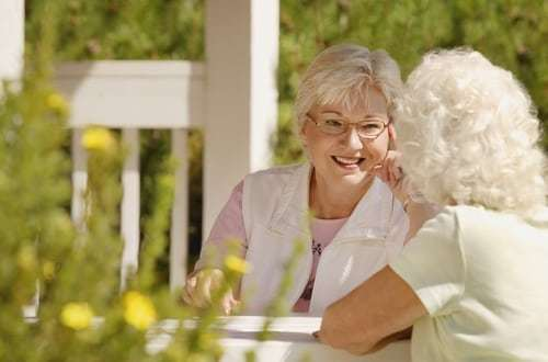 Two senior women talking outside while sitting on patio, yellow flowers