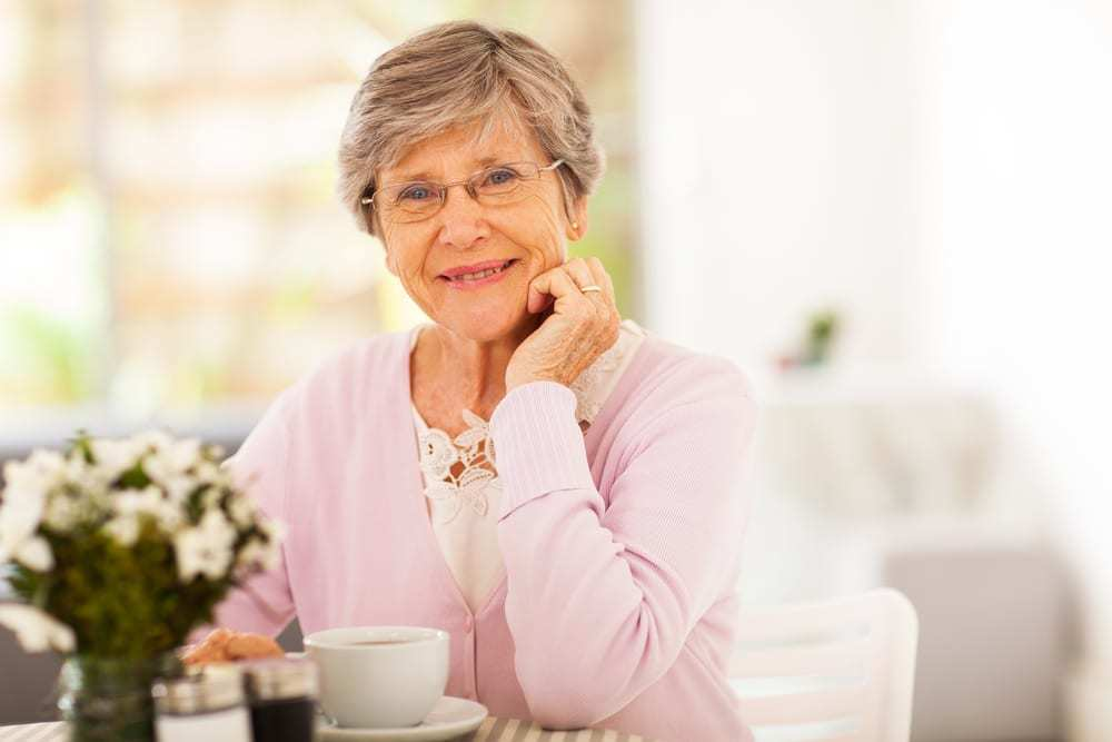 smiling senior woman with a cup of tea at a table