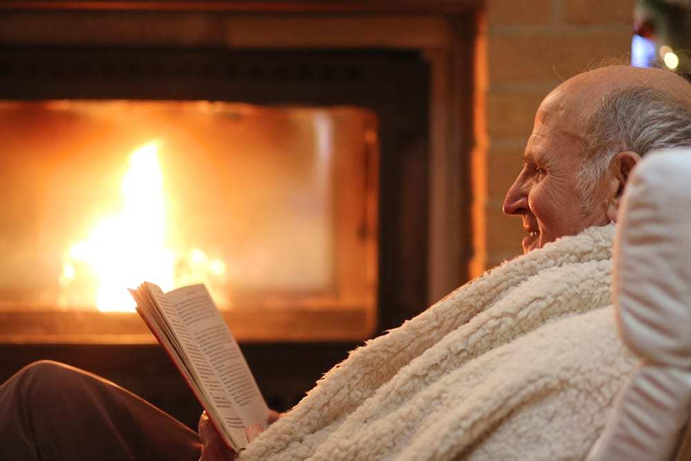Senior man relaxing by fireplace with book and blanket