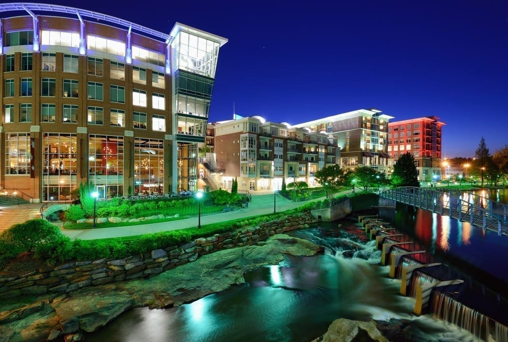 Falls park in Greenville, SC at night near river with buildings in background