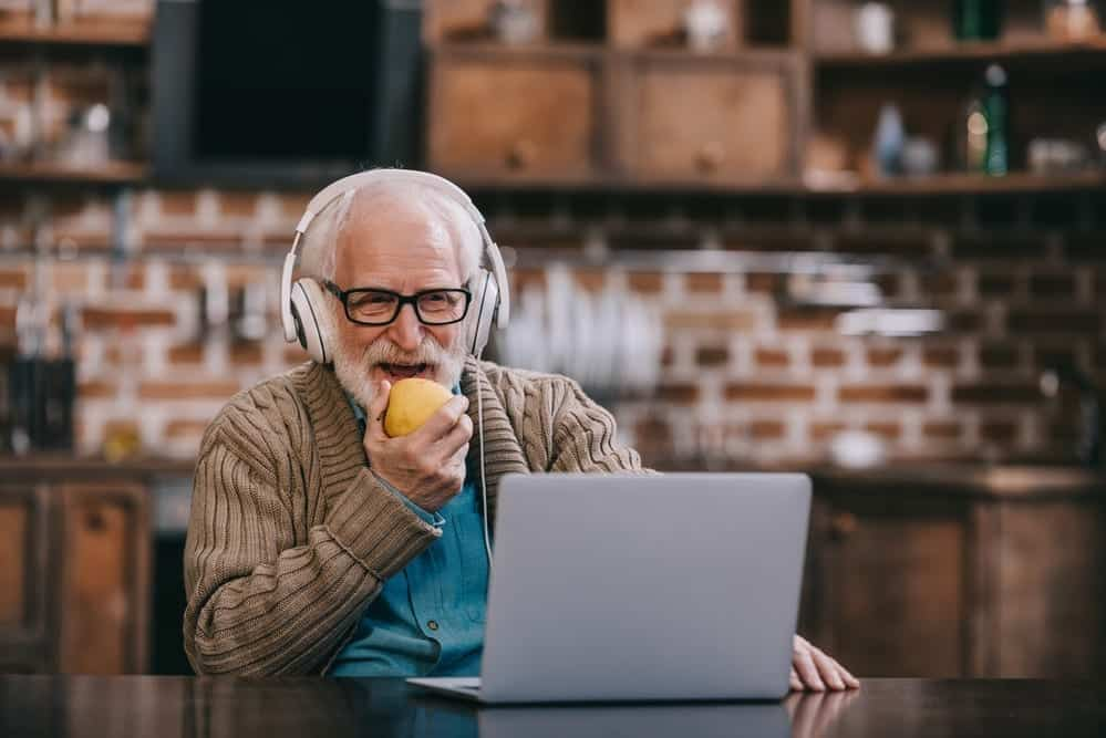 senior man with headphones on, eating apple, talking to someone using his laptop
