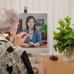 Senior woman taking pill in front of virtual doctor