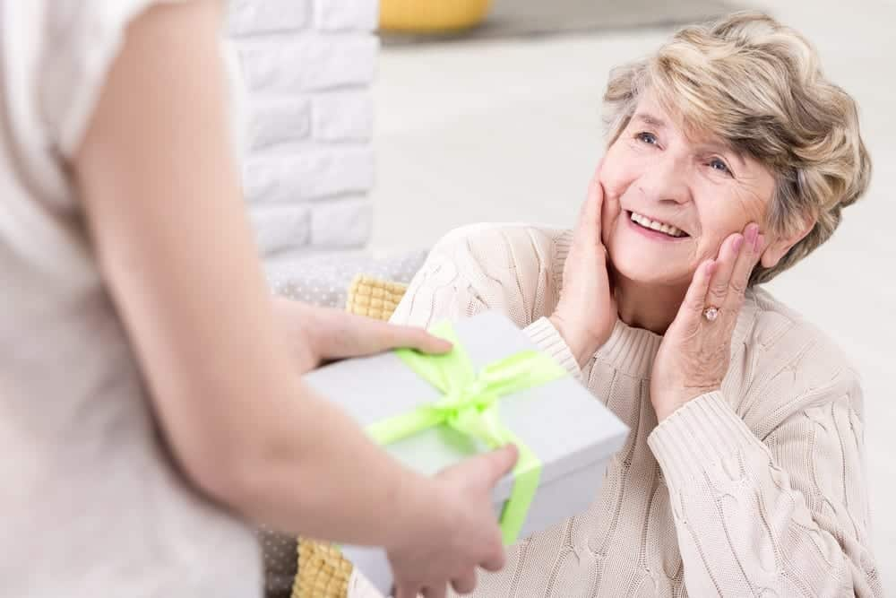 senior woman smiles as she's handed a gift