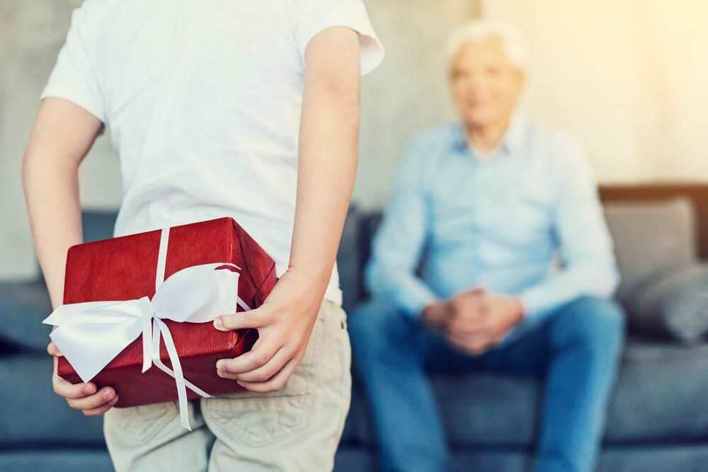 Child holding red present behind back, ready to present to grandfather in background
