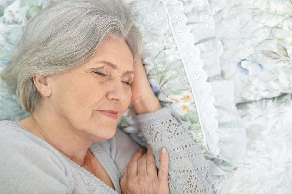 Close-up of senior woman asleep on quilt