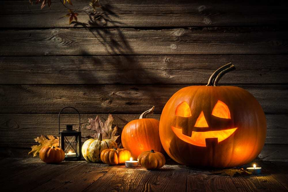 Jack-o-lantern, pumpkins, lantern, and leaves in the dark.jpg