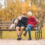 Senior couple with a dog on a bench in the park in autumn