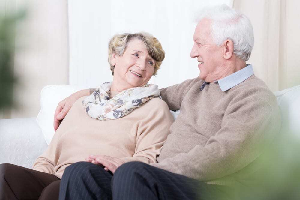 Senior couple sitting on couch, smiling at each other