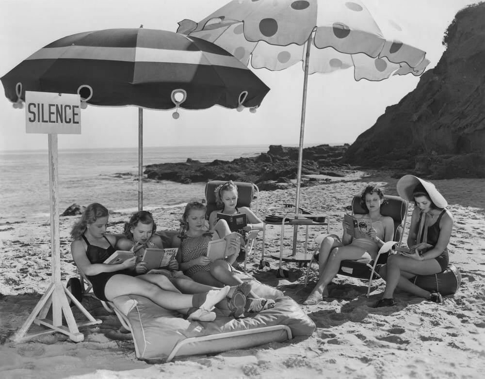 Group of young women reading on the beach in the 1940s or 1950s