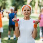 Senior woman in the park lifting handweights