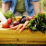 Gardener outside holding wooden box filled with fresh vegetables