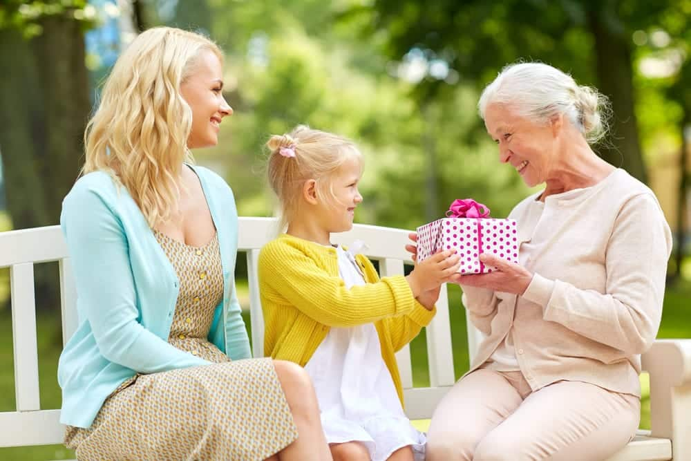 Smiling daughter and granddaughter giving grandma a gift on bench outside