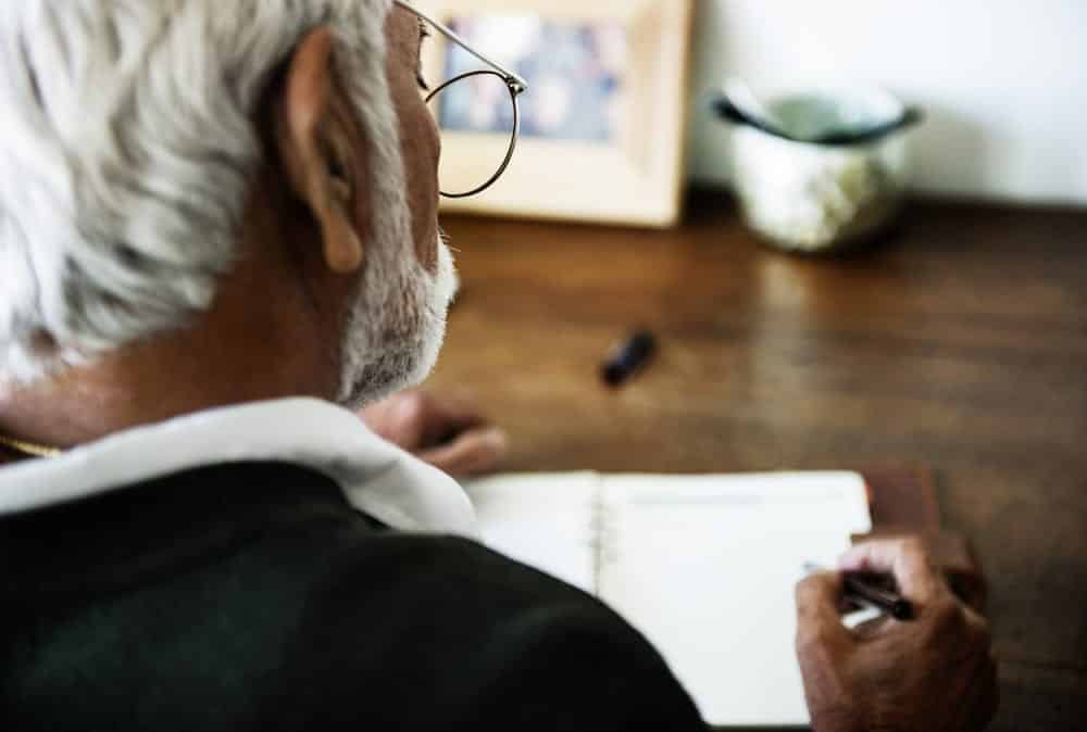 View from over shoulder of senior man writing in journal