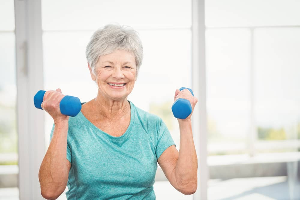 Smiling senior woman lifting small hand weights