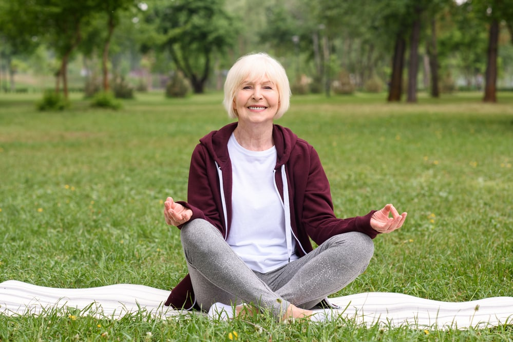 Senior woman in park, sitting cross-legged, smiling, hands positioned on knees