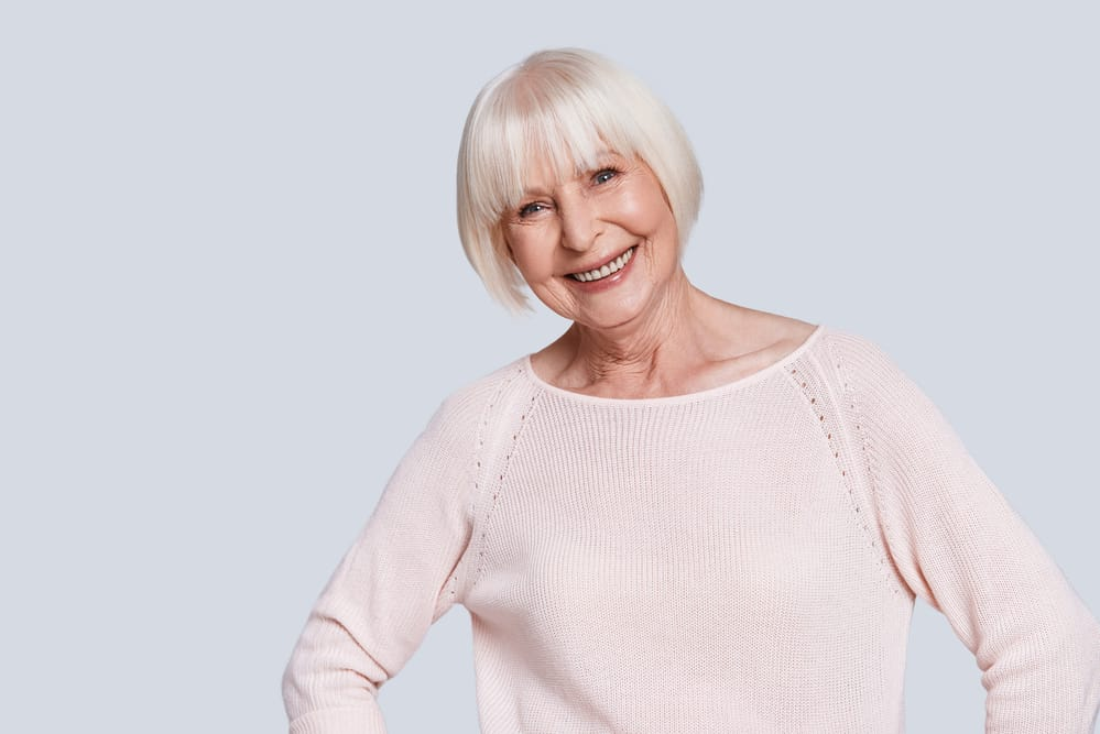 Smiling senior woman in sweater, plain background