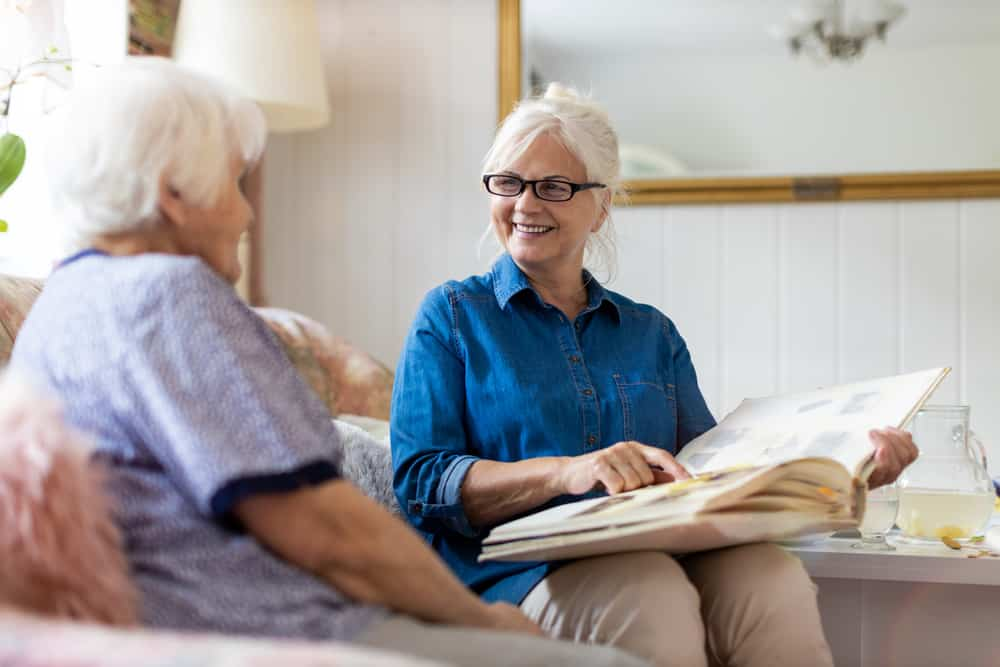Older woman looking at photo album with senior woman, smiling
