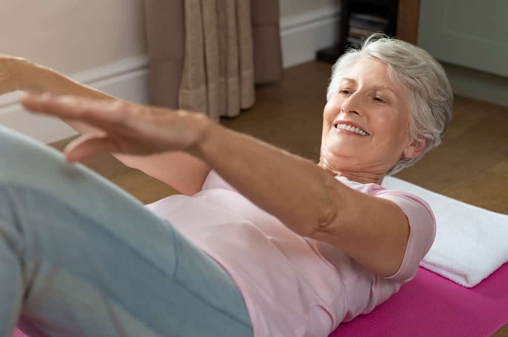 Senior woman doing crunches on yoga mat indoors