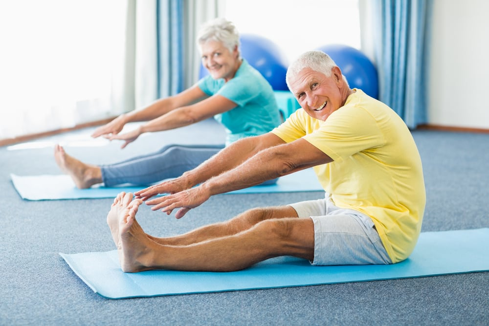 Seniro man and woman stretching to touch their toes in gym