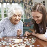 Senior woman and young woman completing puzzle